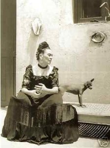 Old black and white photo of lady in dress with Mexican Hairless